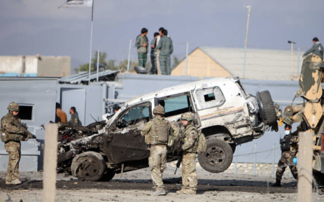 Afghan and foreign security forces investigate the site of a suicide attack targeting a convey near a military camp in the outskirt of Kabul, Afghanistan, on 13 October 2014. Picture: EPA.