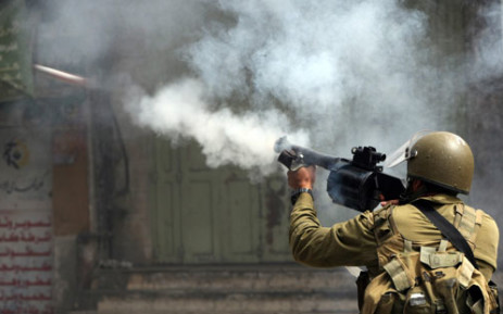 An Israeli soldier fires a tear gas canister during clashes with Palestinian stone throwers in the West Bank city of Hebron.  Picture: Hazem Bader/AFP.