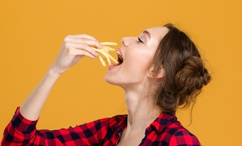 young-woman-placing-chips-in-her-mouth-french-fries2jpg