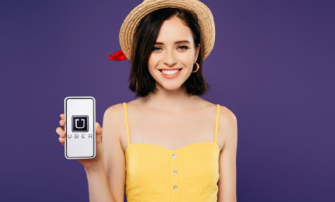 young-woman-holding-smartphone-with-uber-app-open-technology-millenial-123rf