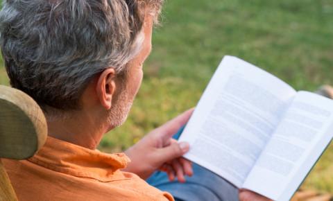 man-reading-book-grey-hair-outside-garden-123rf