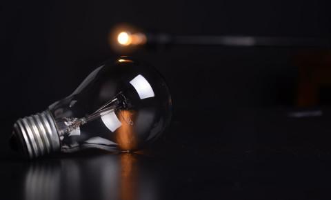Light bulb against dark background, electricity, load shedding. Image: Pexels.
