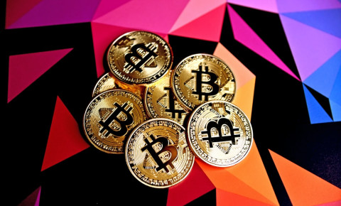 Seven Bitcoin coins on a multi coloured background