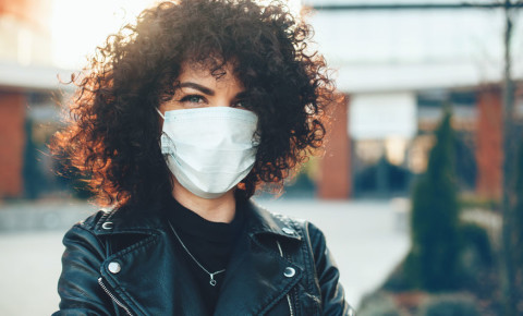 Young attractive woman with curly hair wearing a surgical mask 123rf