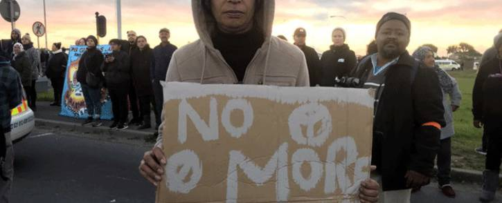 A Bonteheuwel resident stands with a placard during a protest against gang violence on 29 August 2018. Picture: Shamiela Fisher/EWN