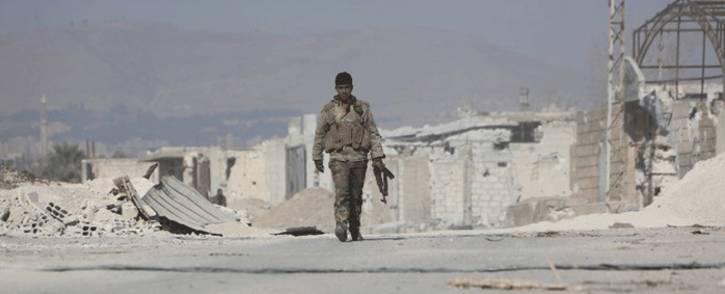 A member of Syria's pro-government forces walks past damaged structures in the town of Mudyara, formerly held by opposition groups, in the centre of the eastern Ghouta region as regime troops carry on with their assault on the rebel-held enclave, just outside the capital Damascus. Picture: AFP