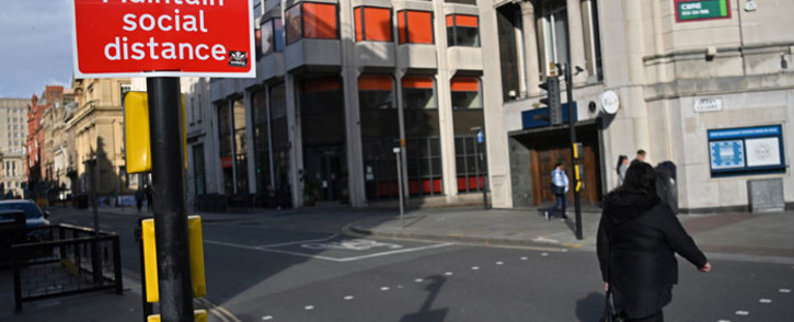 A pedestrian passes a social distancing sign as they cross an empty road in Liverpool, north-west England on 14 October 2020, as new local lockdown measures come in to force to help stem a second wave of the novel coronavirus. Picture: AFP