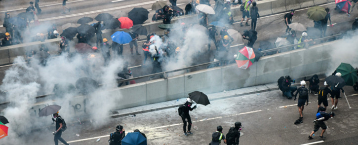 Protesters react after police fired tear near the government headquarters of Hong Kong on 31 August 2019. Thousands of pro-democracy protesters defied a police ban on rallying in Hong Kong on 31 August, a day after several leading activists and lawmakers were arrested in a sweeping crackdown. Picture: AFP.