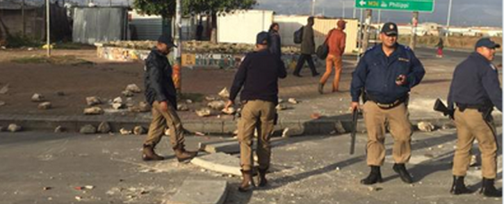 Officers clearing the road of the stones that were thrown by protestors. Picture: Masa Kekana/EWN