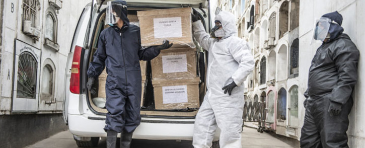 In this file photo taken on 21 May 2020, workers stand next to coffins of COVID-19 victims at El Angel cemetery, in Lima. Peru has adjusted its official coronavirus death toll upward by almost a third from 69,000 to more than 180,000, the government said on 31 May 2021. Picture: Ernesto Benavides/AFP