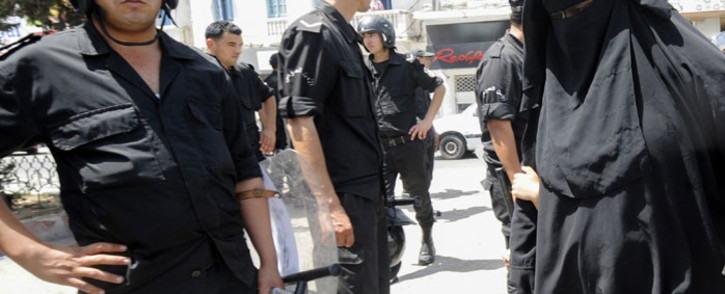 In this file photo taken on 15 June 2012, a Tunisian woman, wearing a niqab, walks in front of police officers after Friday prayers in Tunis. Picture: AFP