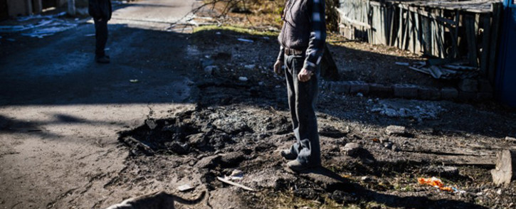 FILE: A man stands next a crater following shelling in Ukraine. Picture: AFP