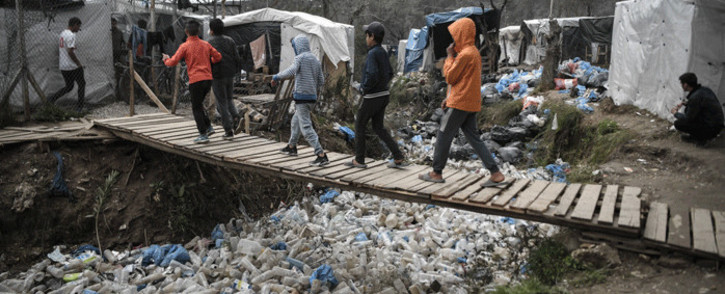 Children walk over a bridge in the Moria migrant camp on the Greek Aegean island of Lesbos on March 5, 2020. Picture: AFP.