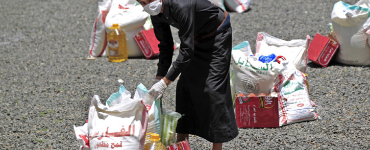 A Yemeni youth carries a portion of food aid, distributed by Yadon Tabney development foundation, in Yemen's capital Sanaa on 17 May 2020. Picture: AFP.