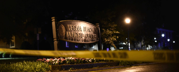 """A police tape blocks the road to access the Virginia Beach municipal centre, the site of a mass shooting, in Virginia Beach, Virginia in the late hours of May 31, 2019. A municipal employee sprayed gunfire """"indiscriminately"""" in a government building complex on Friday in the US state of Virginia, police said, killing 12 people and wounding four in the latest mass shooting to rock the country. Picture: AFP."""