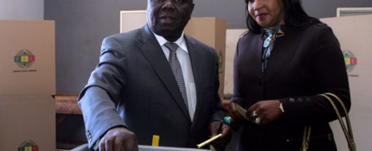 Zimbabwe's Prime minister, leader and candidate of the Movement for Democratic Change (MDC), Morgan Tsvangirai (L), flanked by his wife Elizabeth, casts his ballot in a polling station in Harare July 31, 2013, to vote in a general election. Picture: AFP