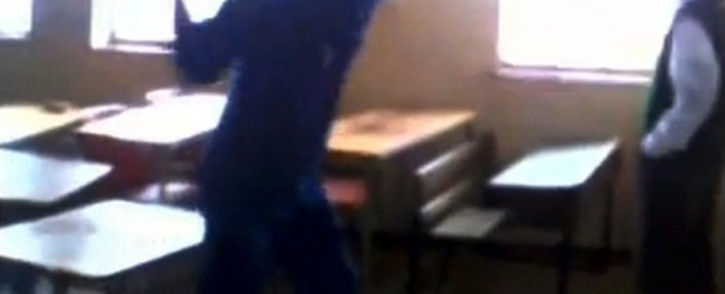 This screengrab from cellphone footage shows a man as he swings a broom at a Stanwest Combined School pupil, 15 May 2014. Picture: 'Standerton Advertiser' via YouTube.
