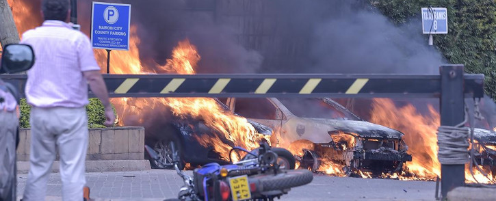 Two men stand next to burning cars at the scene of an explosion at a hotel complex in Nairobi on 15 January 2019. Picture: AFP