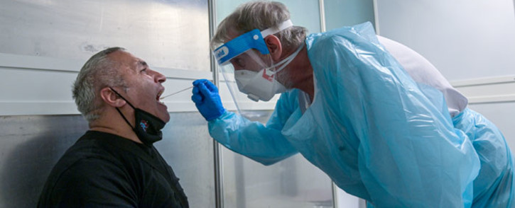 A passenger is tested by a doctor at a coronavirus screening station in the medical center of the airport in Duesseldorf, western Germany, on 27 July 2020. Picture: AFP