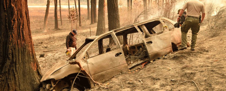 Yuba and Butte County Sheriff officers inspect a burned vehicle after discovering remains nearby in Concow, California, on 11 November 2018 after a camp fire ripped through the area. Picture: AFP