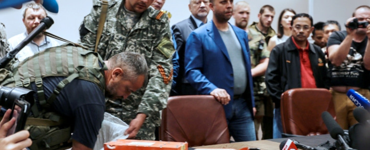 A pro-Russia separatist shows members of the media a black box belonging to Malaysia Airlines flight MH17, before handing it over to Malaysian representatives during a press conference in Donetsk on 22 July 2014. Picture: AFP.