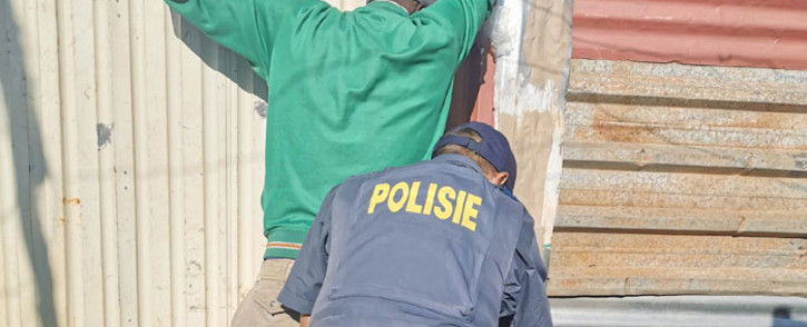 FILE: Police search a resident as part of Operation Okae Molao in the Slovo Park informal settlement, west of Johannesburg on 14 May 2020. Picture: @GP_CommSafety/Twitter.