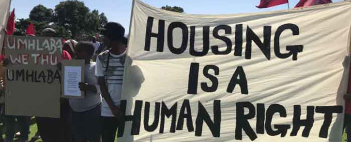 Reclaim the City supporters hold placards during a protest for land to build houses at the Rondebosch Golf Course in Cape Town on Thursday. Picture: @UniteBehind/Twitter.