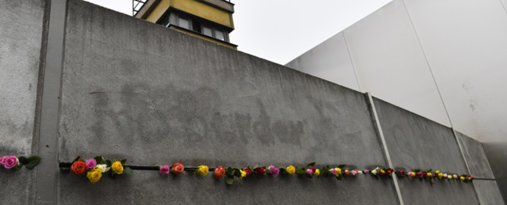 FILE: A picture taken on 9 November 2017 at the Berlin Wall Memorial shows flowers that have been placed in a crack during the commemorations to mark the 28th anniversary of the fall of the Berlin Wall. Picture: AFP.
