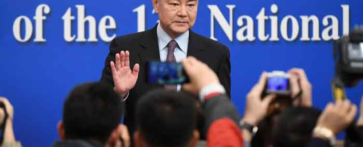FILE: China's Foreign Minister Wang Yi waves to journalists as he arrives for a National People's Congress press conference in Beijing on 8 March 2019. Picture: AFP