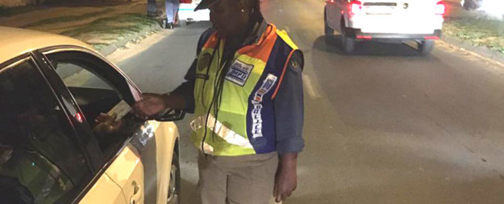 FILE: A JMPD official checks a driver's licence card during a police festive season operation on 20 December 2019. Picture: @WayneMinnaar2/Twitter