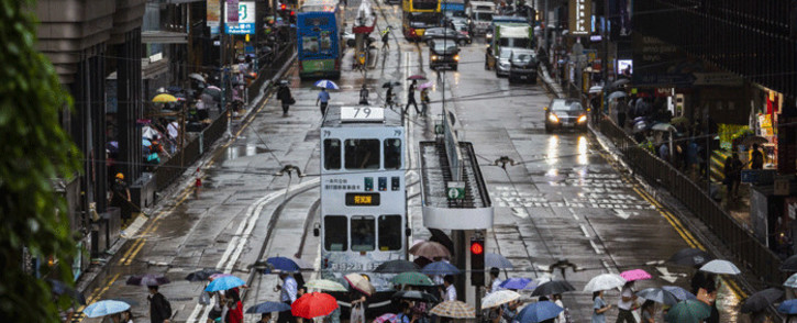 Pedestrians (bottom) with umbrellas cross a road in Hong Kong on July 20, 2021, as weather patterns from Typhoon Cempaka brings heavy rain to the city. Picture: Isaac Lawrence Typhoon Cempaka/ AFP
