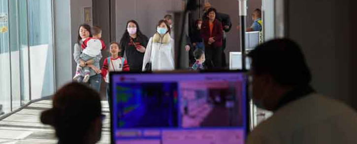 FILE: Health officers screen arriving passengers from China with thermal scanners at Changi International airport in Singapore on 22 January 2020 as authorities increased measure against coronavirus. Picture: AFP.