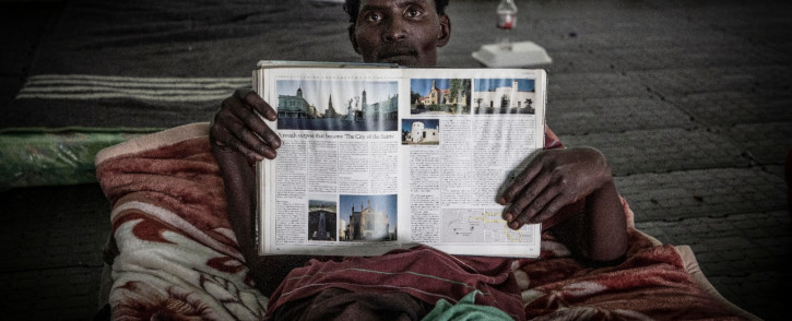 A homeless men sits on his mattress reading a book. Picture: Abigail Javier/EWN