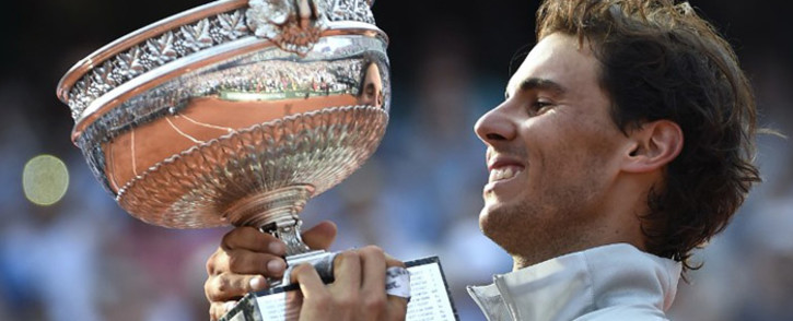 Spain's Rafael Nadal holds the Musketeers trophy after winning the French tennis Open men's final match against Serbia's Novak Djokovic at the Roland Garros stadium in Paris on 8 June, 2014. Picture: AFP.