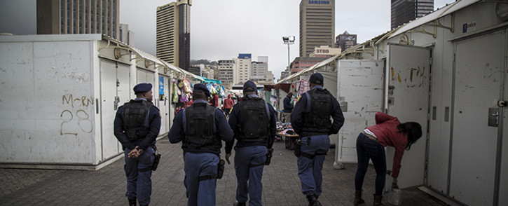 Saps officers patrol the station deck in Cape Town during an operation in the CBD. Picture: Thomas Holder/EWN