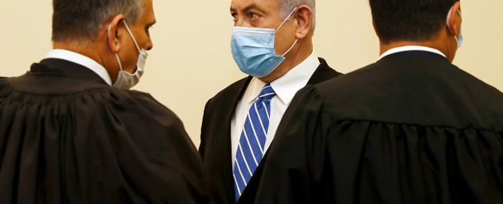 Israeli Prime Minister Benjamin Netanyahu (C), wearing a protective face maks, is pictured inside a courtroom at the district court of Jerusalem on 24 May 2020, during the first day of his corruption trial. Picture: AFP.