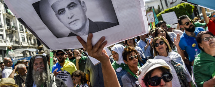 FILE: An Algerian protester marches with a sign showing the portrait of political activist Kamel Eddine Fekhar, who died days earlier, during a demonstration in the capital Algiers on 31 May 2019. Picture: AFP