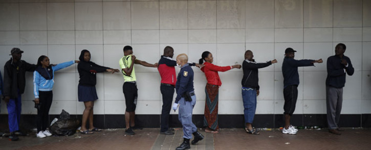 A member of the South African Police Service (SAPS) enforces social distancing as he makes shoppers hold their hands out in front of them to ensure that they are at least one metre apart from one another while they queue outside a supermarket in Yeoville, Johannesburg, on 28 March 2020. Picture: AFP