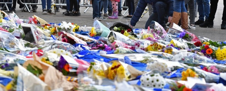 A man adds flowers to a growing pile of tributes outside Leicester City Football Club's King Power Stadium in Leicester, eastern England, on 28 October 2018 after a helicopter belonging to the club's Thai chairman Vichai Srivaddhanaprabha crashed outside the stadium the night before. Picture: AFP.