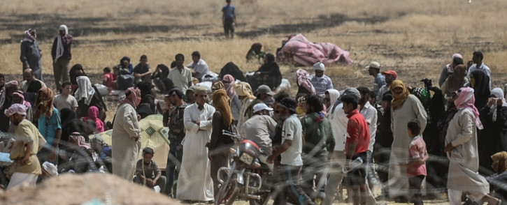 FILE: Syrian refugees wait between Syria and Turkish border as Turkish soldiers block them to pass the Turkish side, on 9 June, 2015, at Akcakale, in Sanliurfa province. Picture: AFP.