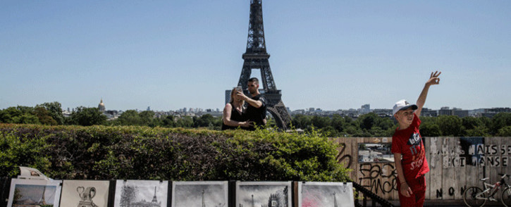 Tourists take a selfie under a blue sky with the Eiffel Tower behind and drawings in the front at the Trocadero Square, in Paris, on June 13, 2021. Picture: Sameer Al-Doumy / AFP