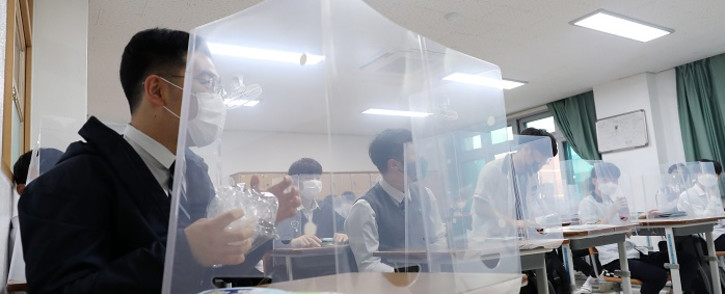 Students sit behind protective shields as a preventative measure against the COVID-19 novel coronavirus in a classroom in Daejeon on 20 May 2020. Picture: AFP