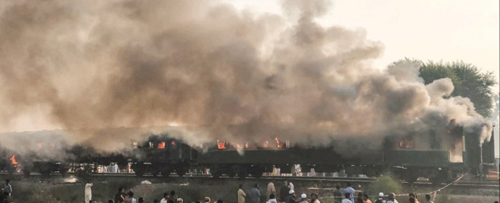 In this handout picture taken and release by Punjab Emergency Service Rescue 1122 on October 31, 2019, residents gather beside the burnt-out train carriages after a passenger train caught on fire near Rahim Yar Khan in Punjab province on October 31, 2019. Picture: AFP/ Pakistan's Punjab Emergency Service Rescue 1122.