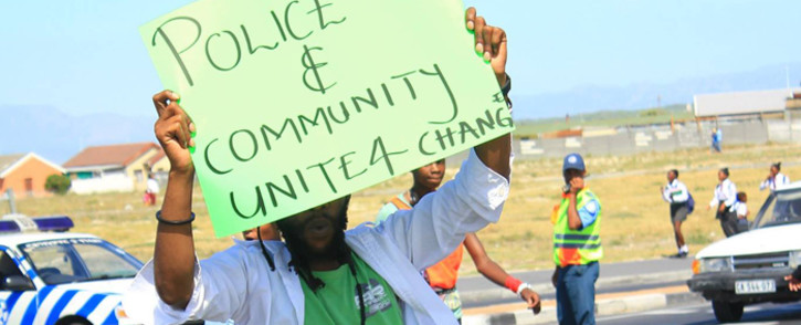 FILE. An activist carry a placard he protests against policing in Khayelitsha. Picture: Ndifuna Ukwazi Facebook page.