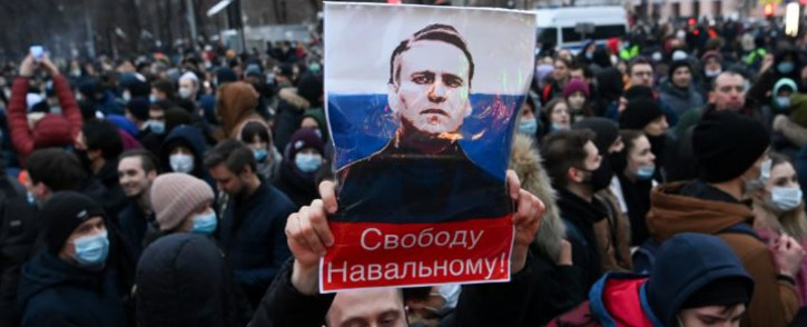 """FILE: Protesters march in support of jailed opposition leader Alexei Navalny in downtown Moscow on 23 January 2021. The placard with an image of the Kremlin critic reads """"Freedom to Navalny!"""". Picture: Kirill KUDRYAVTSEV/AFP"""