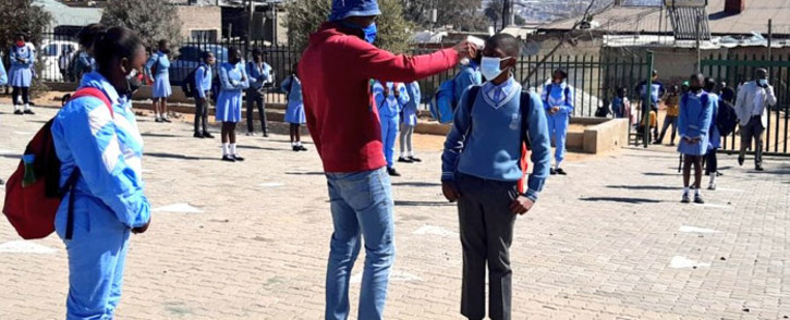A pupil has his temperature taken at the Iphuteng Primary School in Alexandra, Johannesburg on 24 August 2020. Picture: @educationgp/Twitter
