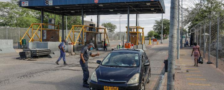FILE: A South African Police Service officer interacts with a driver who's crossing from Zimbabwe into South Africa using the Beitbridge border post, near Musina, South Africa, on 8 January 2021. Picture: AFP.