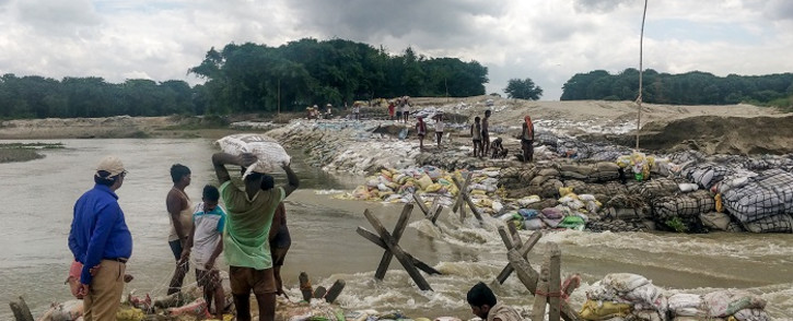 Locals gather concrete fragments and heavy bags wrapped in nets to build a dam as floodwaters flow from the north into the state of Indian eastern state of Bihar near Muzaffarpur on 13 July 2019. Picture: AFP