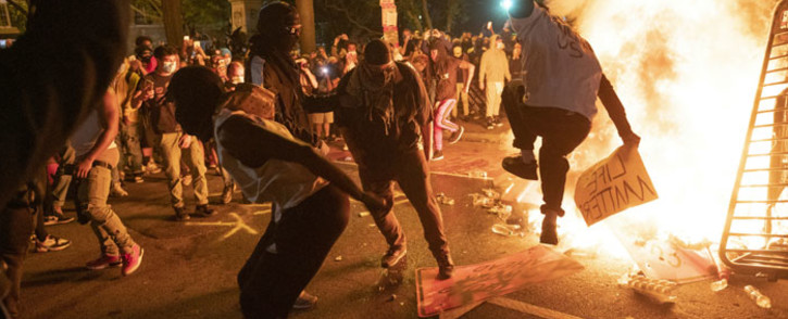 Protesters jump on a street sign near a burning barricade during a demonstration against the death of George Floyd near the White House on 31 May 2020 in Washington, DC. Picture: AFP