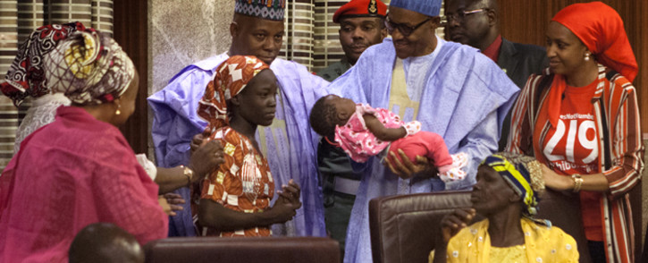 Nigerian President Mohammadu Buhari holds the daughter of the kidnapped Chibok schoolgirl Amina Ali as Borno state governor Kashim Shettima (C) looks on at her arrival at the presidency in Abuja, on 19 May, 2016. Picture: AFP.